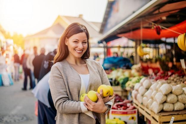 Femme commerçante achetant des fruits au marché.