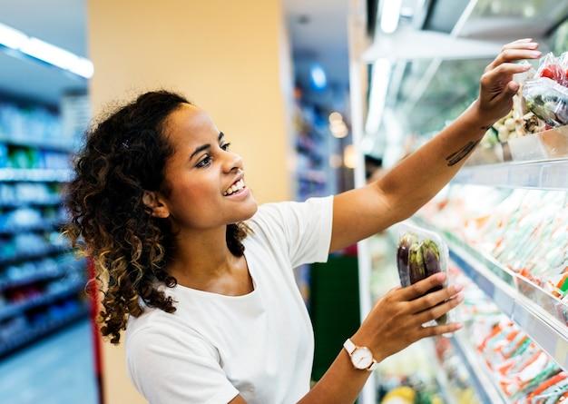 Femme commerçante de légumes au supermarché