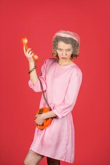 Femme de communication parlant au vieux téléphone femme en robe rose avec combiné téléphonique femme heureuse