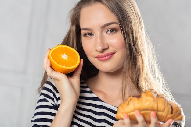 Femme, comparaison, gâteau malsain, fruit orange