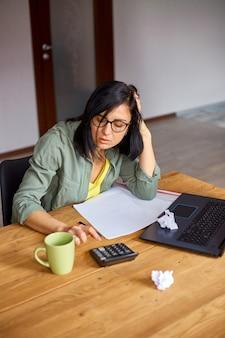Une femme comptable s'assoit pour calculer les dépenses sur une calculatrice à une table en bois, lieu de travail moderne
