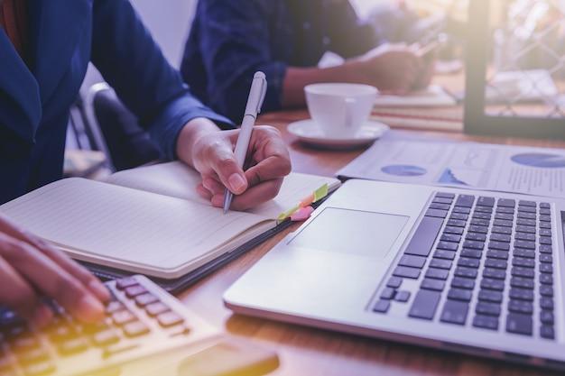 Femme comptable travaillant à l'aide d'une calculatrice pour calculer un rapport financier sur le lieu de travail.