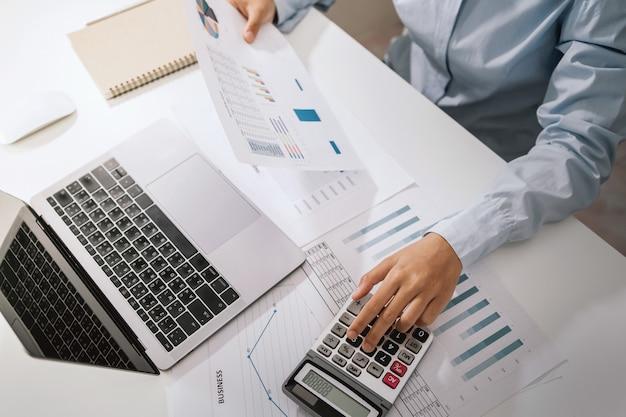 Une femme comptable utilise une calculatrice et un ordinateur avec un stylo sur le bureau au bureau. concept financier et comptable