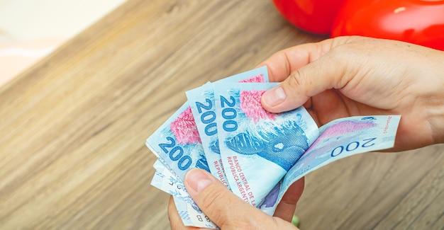 Une femme comptant des billets d'argent argentins
