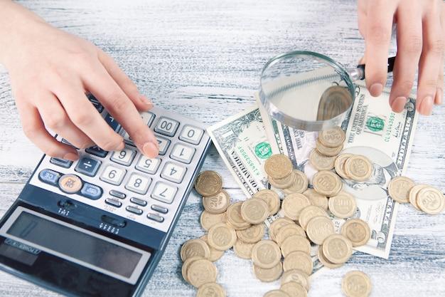 La femme compte l'argent avec la calculatrice et regarde avec une loupe