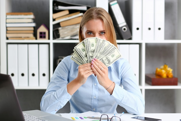 Femme compte des billets de cent dollars