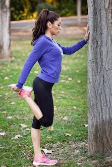 Femme concentré tendant la jambe droite