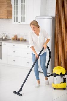 Femme concentrée sur les adultes en chemisier et jeans à l'aspirateur sur le sol blanc à la maison dans la cuisine