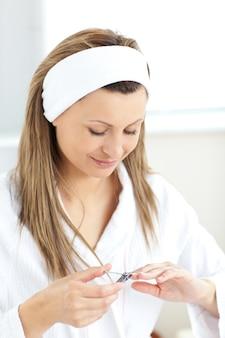 Femme concentrée à l'aide d'un ciseaux à ongles