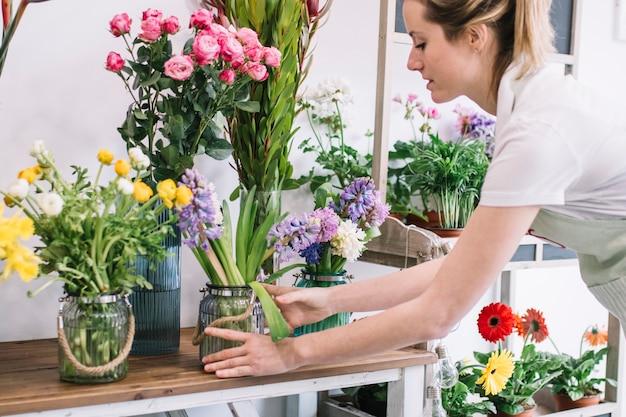 Femme concentrée, arrangeant des fleurs dans la boutique