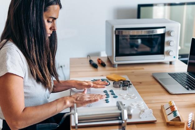 Femme concentrée créant des bijoux artisanaux colorés à la maison avec de l'argile et utilisant des outils.