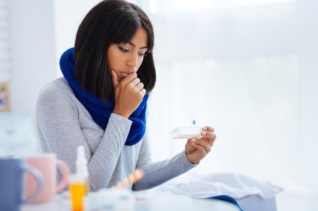 Femme concentrée. femme malade calme attentif regardant pensivement la minuscule boîte à pilules dans ses mains