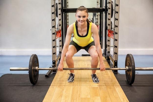 Femme concentrée sur le point de soulever une barre et des poids