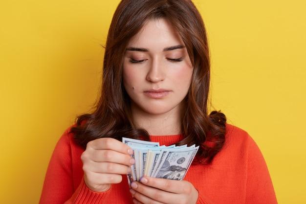 Femme concentrée portant un cavalier décontracté orange tenant des billets en mains