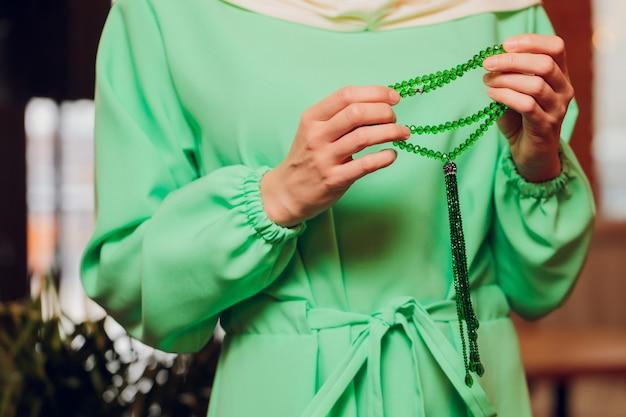Femme concentrée priant portant des perles de chapelet. namaste. gros plan des mains.