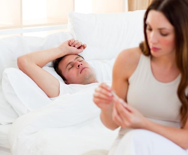 Femme concernée prenant la température de son mari malade