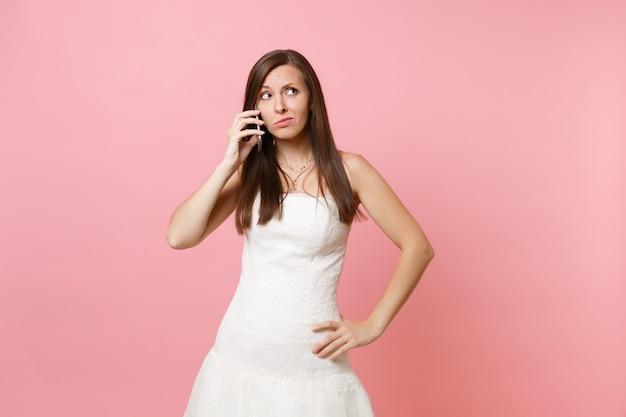 Femme concernée en robe blanche recherchant et parlant au téléphone mobile