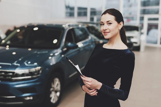 Femme concessionnaire automobile en robe noire auto salon.