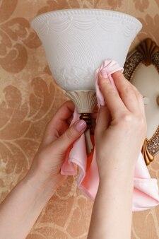 Femme concierge, nettoyage de la lumière électrique à la maison