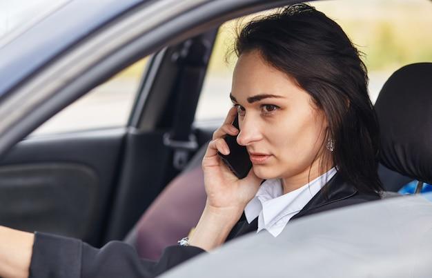 Une femme conductrice à l'aide de son téléphone portable en conduisant une voiture