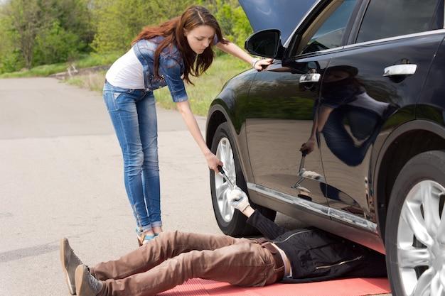 Femme conductrice regardant un mécanicien réparer sa voiture