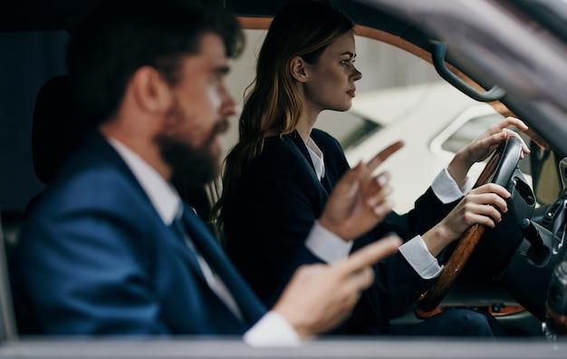 Une femme conduisant une voiture à côté d'un homme collègues à des fonctionnaires de voyage de travail