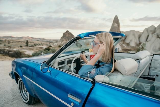 Femme conduisant une voiture décapotable bleue classique en turquie
