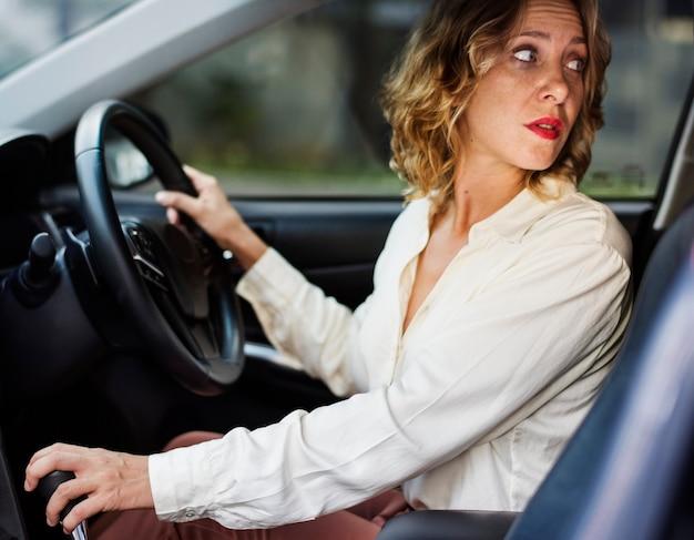 Femme conduisant une voiture en marche arrière