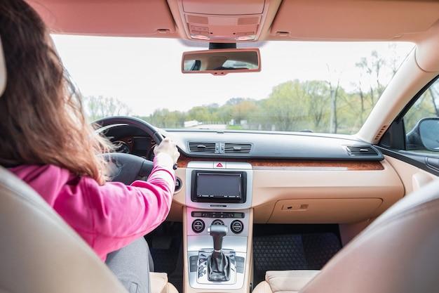 La femme conduisant la voiture moderne sur la route goudronnée vers le coucher du soleil