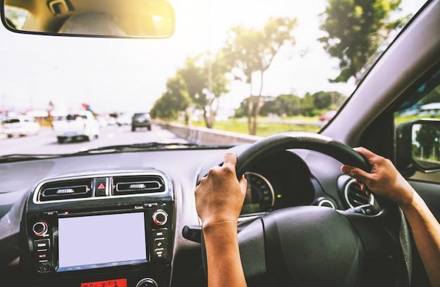 Femme conduisant avec la voiture