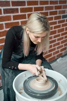 Femme, confection, céramique, poterie, roue, mains, closeup concept pour femme en freelance, business, hobby