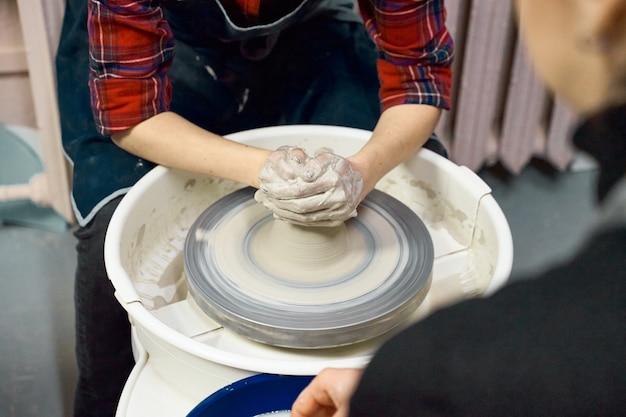 Femme, confection, céramique, poterie, roue, mains, closeup concept pour femme en freelance