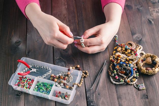 Femme, confection, perlé, bracelet, mains