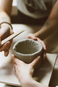 Femme, confection, poterie céramique, quatre mains, gros plan, foyer, sur, potiers, paumes, à, poterie