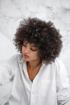 Femme confiante aux cheveux bouclés posant