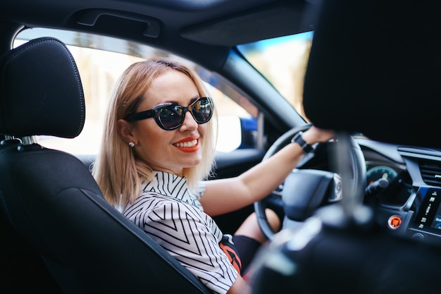 Femme confiante et belle à lunettes de soleil. vue arrière de la jolie jeune femme en tenue décontractée au volant d'une voiture