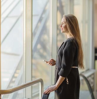 Femme confiante à la fenêtre en verre extérieur