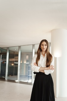 Femme confiante en jupe longue noire et chemisier blanc, croise les mains sur sa poitrine dans une pose sûre d'elle-même.