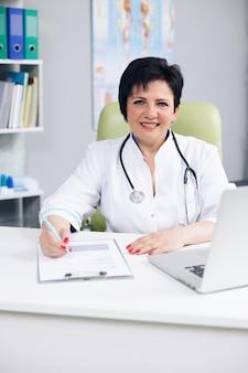 Une femme confiante porte une blouse médicale blanche avec un stéthoscope regardant à l'avant