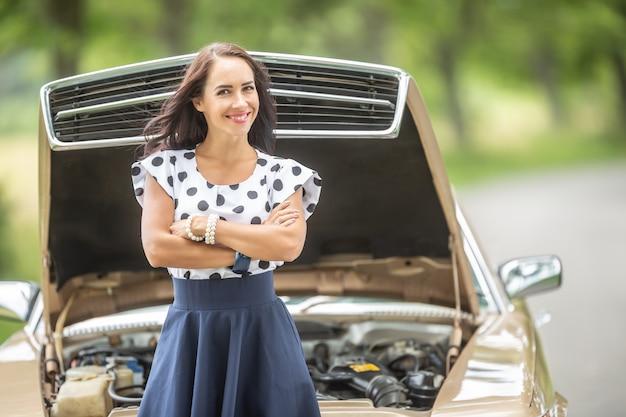 Une femme confiante se tient devant une voiture avec le capot ouvert, les bras croisés, souriant à la caméra.