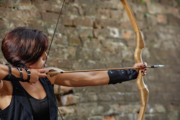 Femme confiante tirant de l'arc, se focaliser, détourner les yeux.