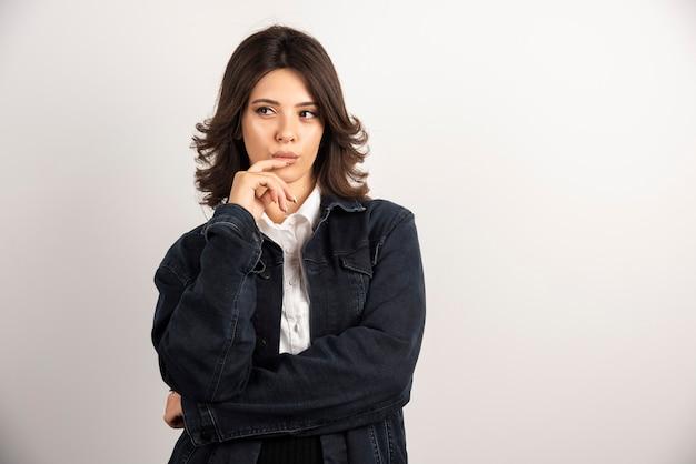 Femme confiante en veste en jean debout sur blanc.