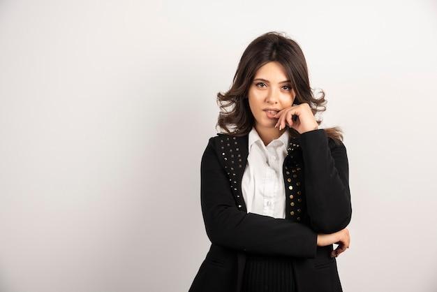 Femme confiante en veste noire debout sur blanc