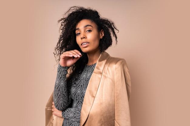 Femme confiante en veste de soie dorée et robe sexy brillante avec un corps bronzé parfait posant