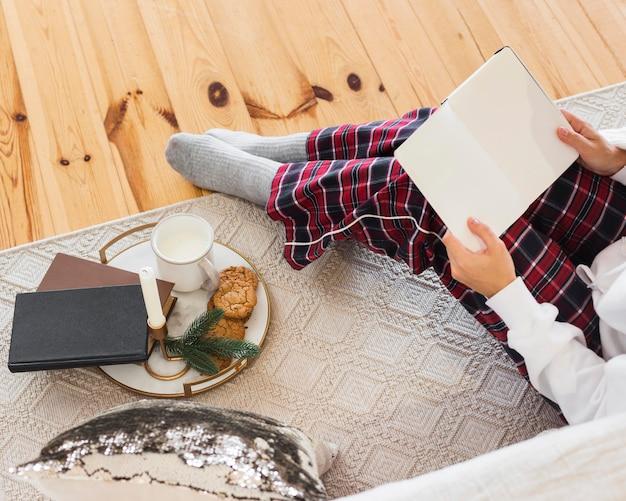 Femme confortable à angle élevé assis sur un tapis avec livre