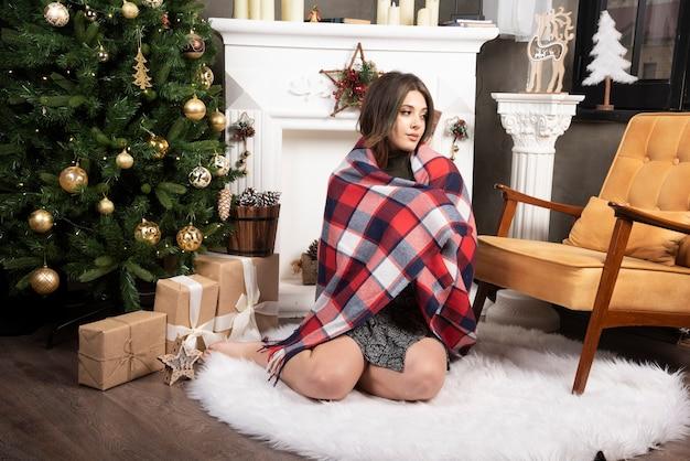 Femme confortable avec écharpe assise sur un tapis blanc près de la cheminée