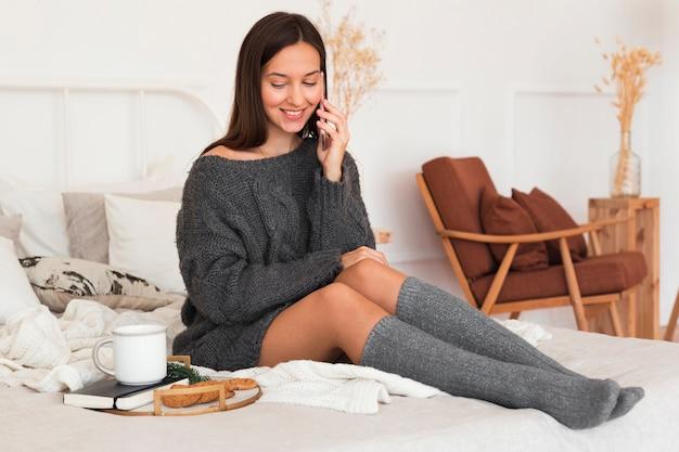 Femme confortable plein coup assis sur le lit avec du lait, des biscuits et de l'ordre du jour