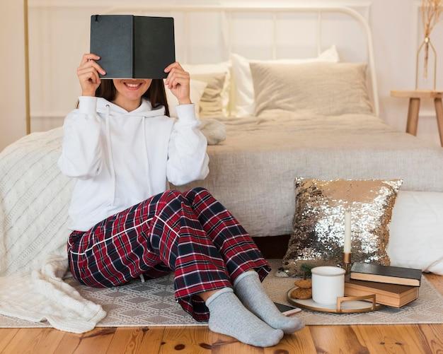 Femme confortable plein coup assis sur un tapis avec livre et collation