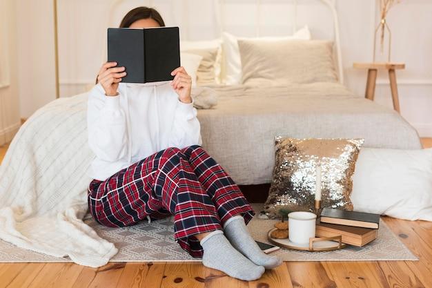 Femme confortable plein coup assis sur un tapis avec livre