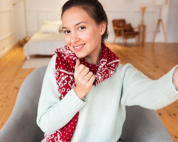 Femme confortable prenant selfie avec écharpe